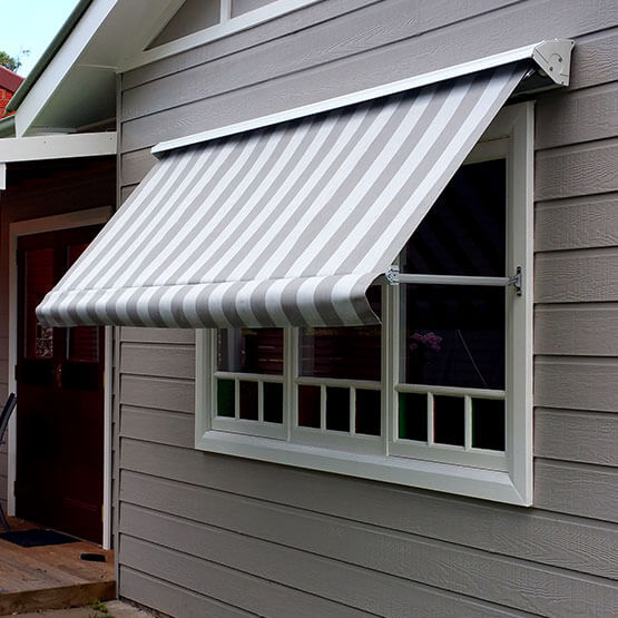 Pivot arm awning shielding a canberra home window