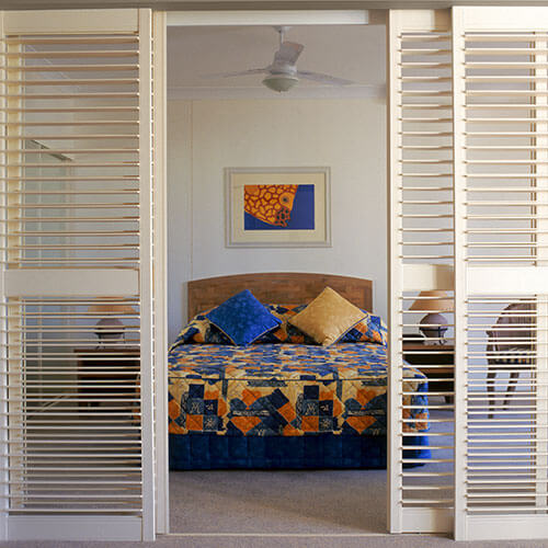 An image of a bedroom framed by timber shutter blinds in Canberra